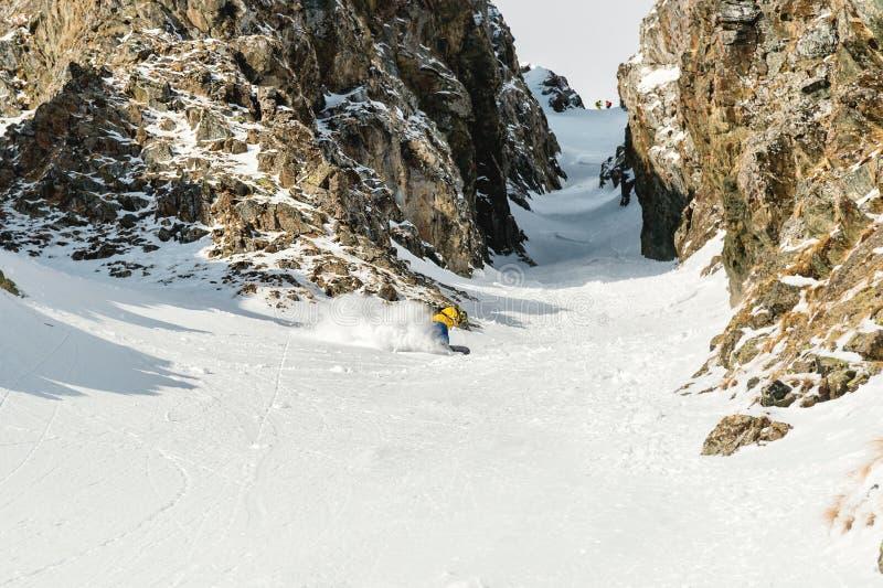 Um homem um snowboarder freerider desce um backcountry na alta velocidade de uma inclinação imagens de stock royalty free