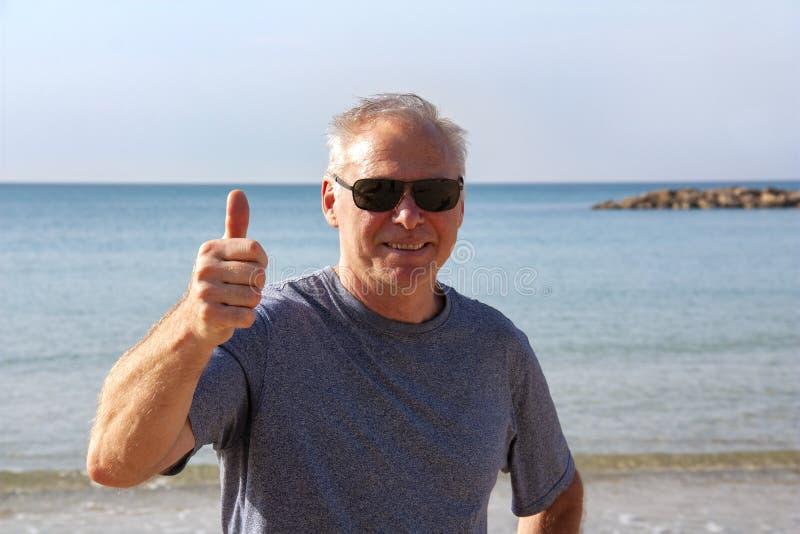 Um homem sobre 60 anos mostra um gesto toda direito imagens de stock