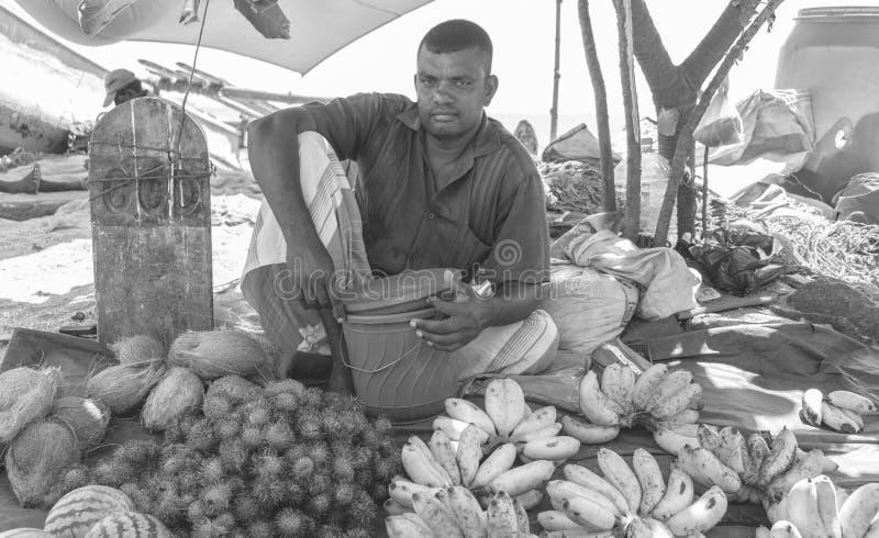 Um homem sorridente vendendo frutas na praia imagem de stock