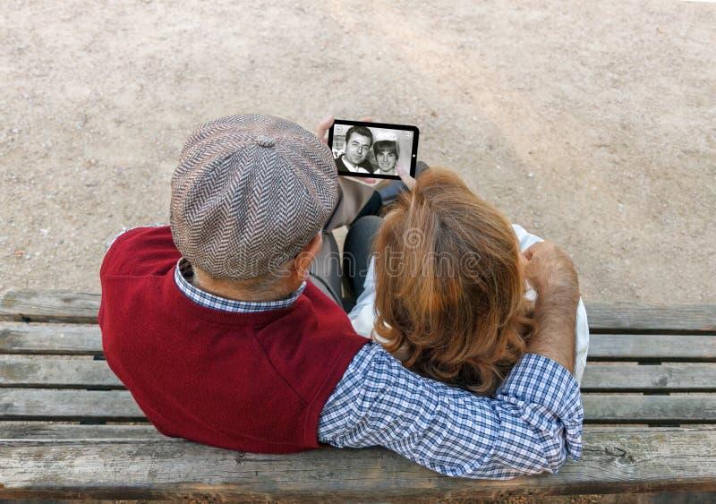 Um homem superior e uma mulher entregam usando um telefone celular do écran sensível imagens de stock