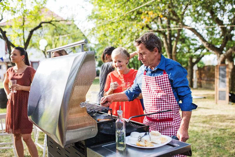 Um homem superior que cozinha o alimento na grade em um partido do assado fora no quintal imagens de stock royalty free