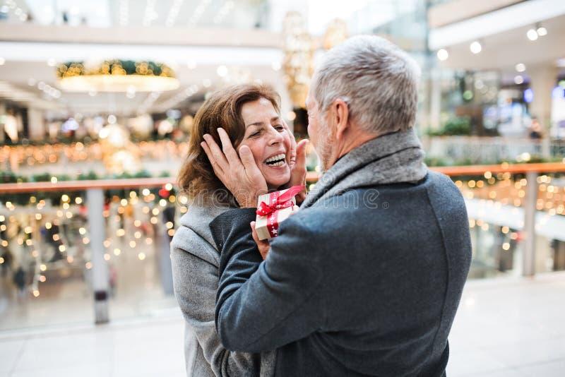 Um homem superior que dá um presente a uma mulher no shopping no tempo do Natal fotografia de stock