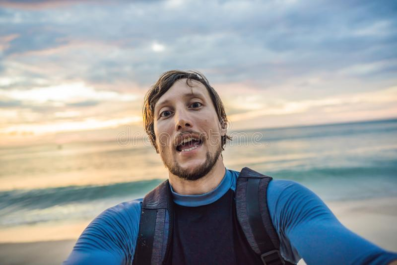 Um homem toma um selfie no fundo do mar e do por do sol fotografia de stock