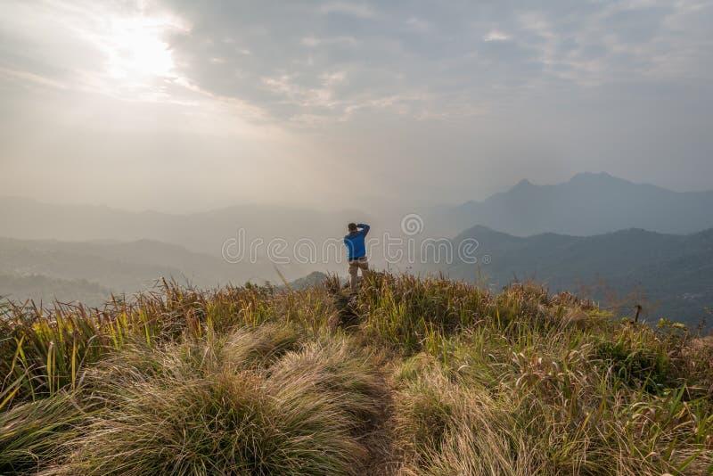 Um homem toma uma foto na parte superior do fá em Chiang Rai, Thail do qui de Phu fotografia de stock