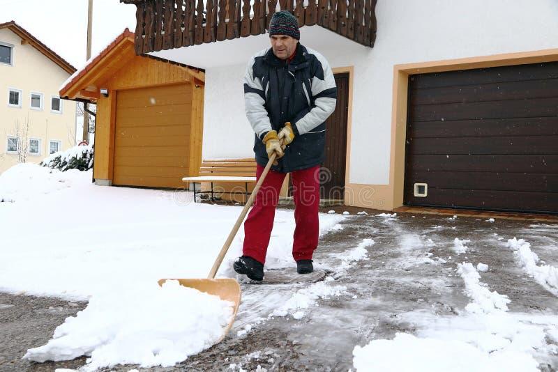 Um homem trabalha com pá a neve na frente das garagens foto de stock