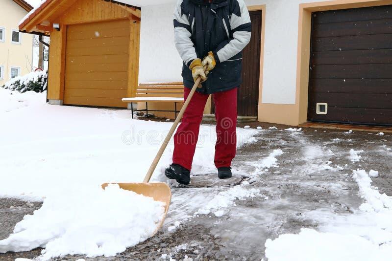 Um homem trabalha com pá a neve na frente das garagens fotos de stock