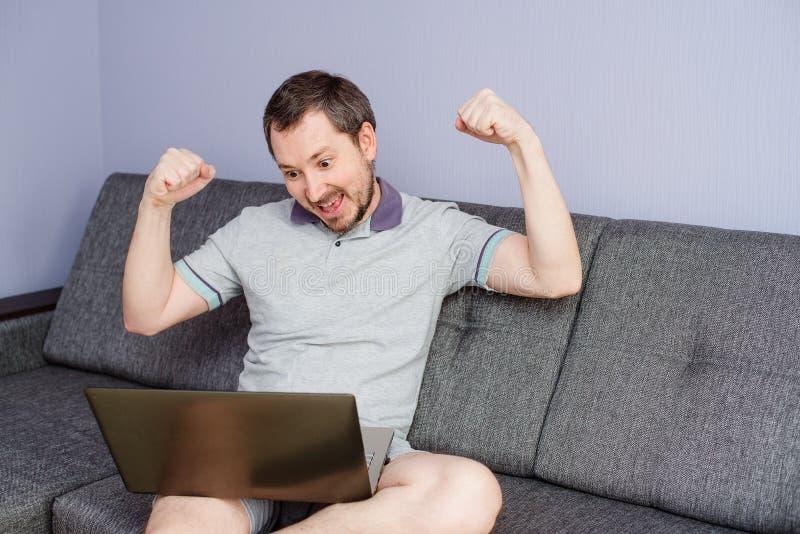 Um homem trabalha em casa atrás de um laptop foto de stock royalty free