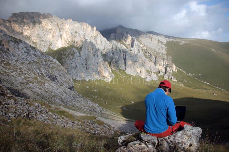 Um homem trabalha em um portátil que senta-se sobre uma montanha foto de stock