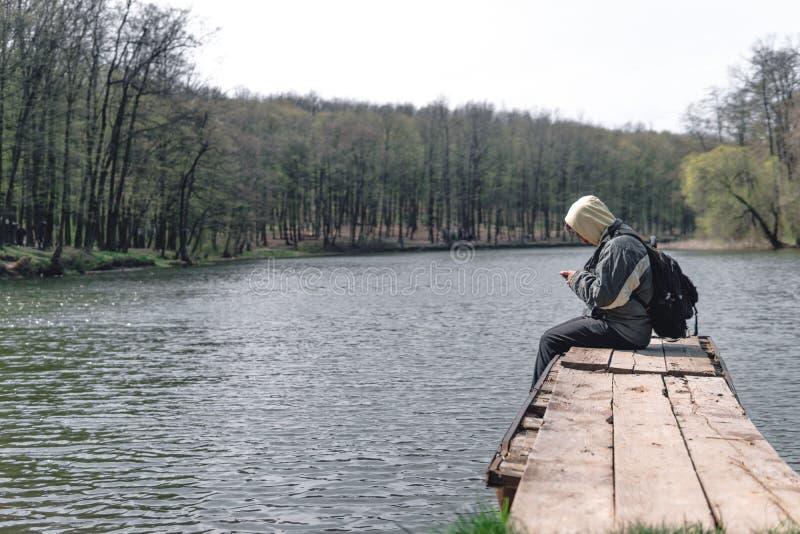 Um homem triste est? sentando-se apenas no cais pelo lago Floresta no fundo capa em sua cabe?a backpack no telefone da posse das  fotos de stock royalty free