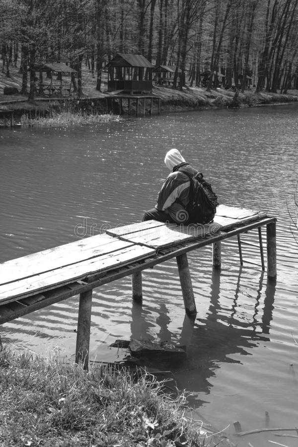 Um homem triste est? sentando-se apenas no cais pelo lago Floresta preto e branco capa em sua cabe?a backpack no telefone da poss foto de stock