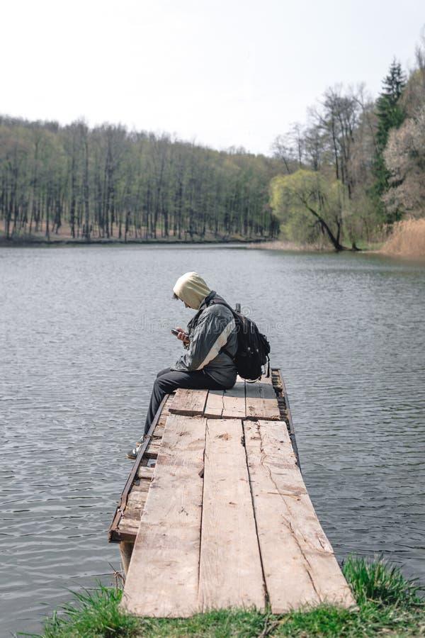 Um homem triste est? sentando-se apenas no cais pelo lago Floresta no fundo capa em sua cabe?a backpack no telefone da posse das  imagens de stock royalty free