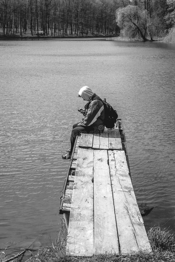 Um homem triste est? sentando-se apenas no cais pelo lago Floresta preto e branco capa em sua cabe?a backpack no telefone da poss fotos de stock