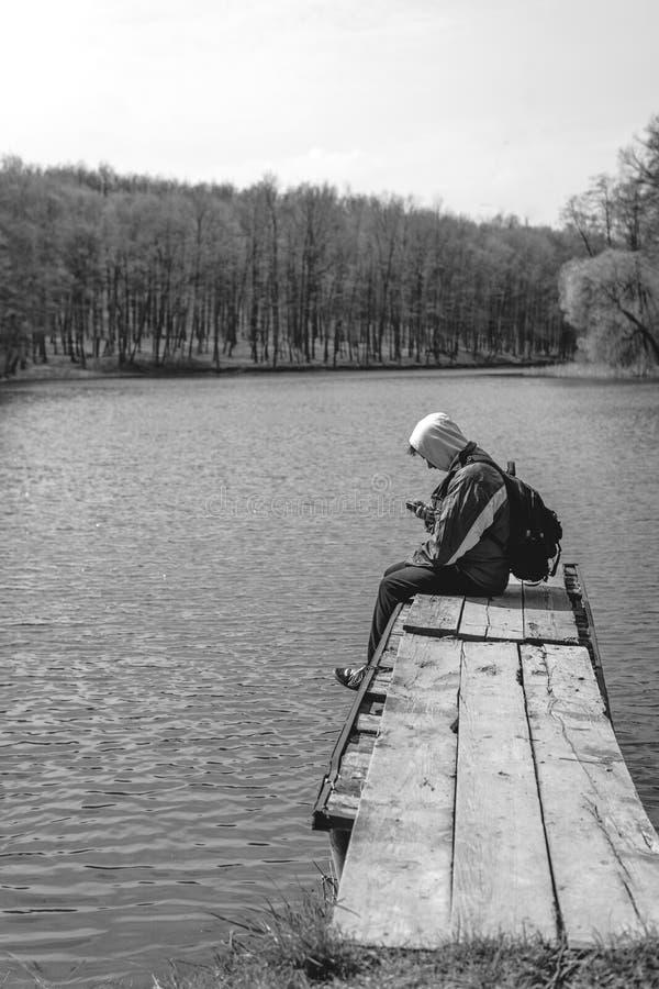 Um homem triste est? sentando-se apenas no cais pelo lago Floresta preto e branco capa em sua cabe?a backpack no telefone da poss fotos de stock royalty free