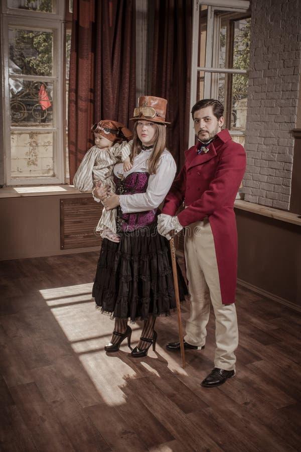Um homem, uma mulher e uma criança, vestidos na roupa do estilo do steampunk foto de stock royalty free