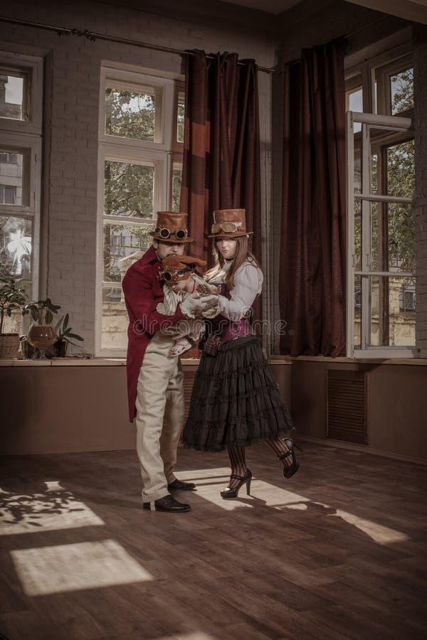 Um homem, uma mulher e uma crian?a, vestidos na roupa do estilo do steampunk fotos de stock