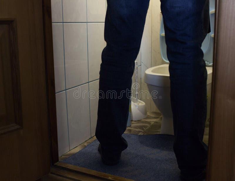 Um homem urina no toalete, nos pés do ` s dos homens, nos problemas de saúde, na prostatite e no adenoma fotografia de stock