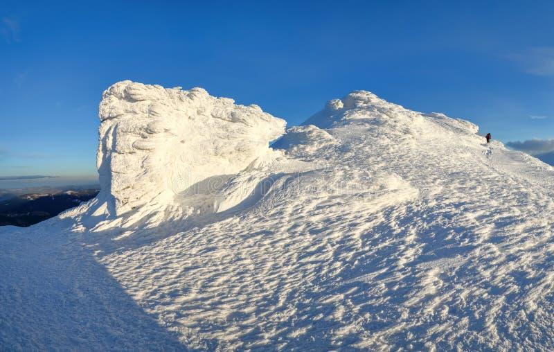 Um homem vai ao longo do trajeto com uma trouxa Rochas fantásticas misteriosas congeladas com gelo e neve de formulários estranho imagem de stock royalty free