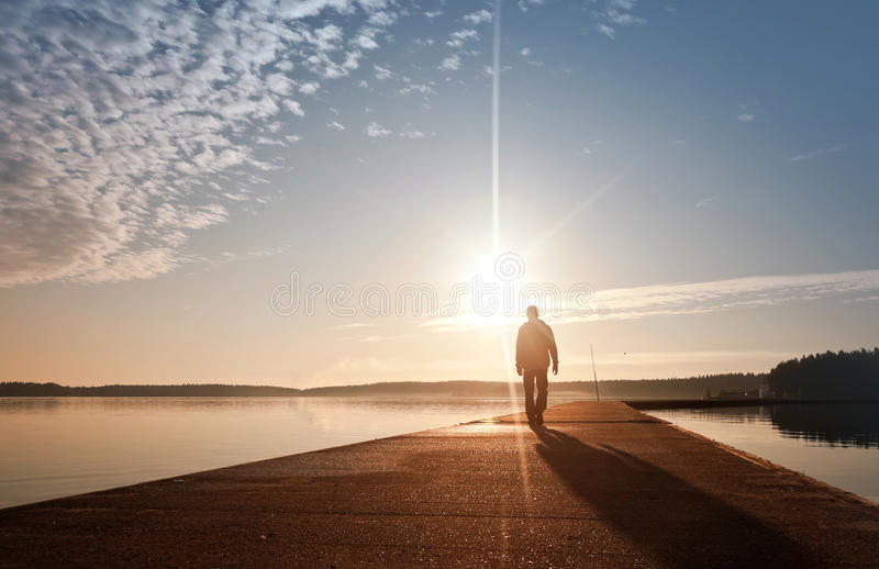 Um homem vai no cais no nascer do sol imagem de stock royalty free