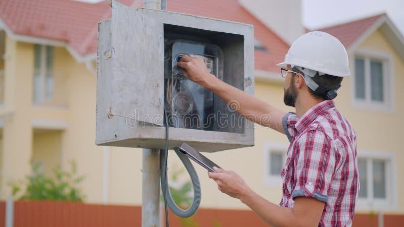 Um homem verifica a eletricidade da leitura de medidor na casa de campo fotos de stock royalty free