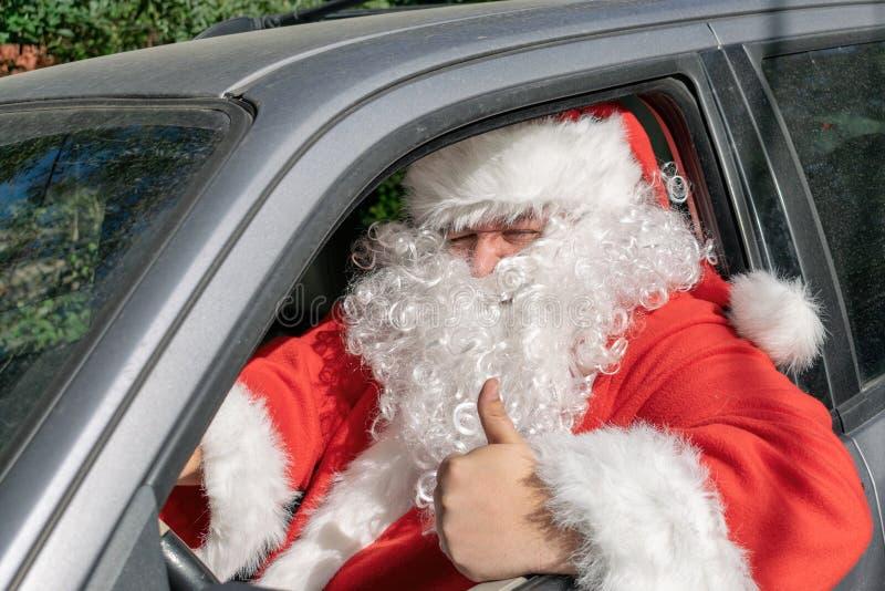 Um homem vestido como Santa Claus entrega presentes no carro Problemas do esforço e da estrada foto de stock royalty free