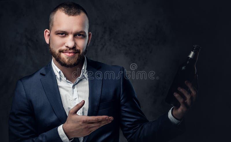 Um homem vestiu-se em um terno elegante guarda a cerveja do ofício fotos de stock