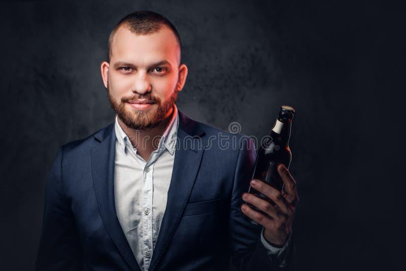Um homem vestiu-se em um terno elegante guarda a cerveja do ofício foto de stock royalty free