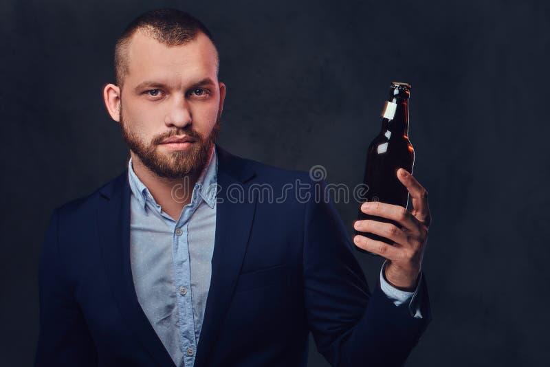 Um homem vestiu-se em um terno elegante guarda a cerveja do ofício imagens de stock