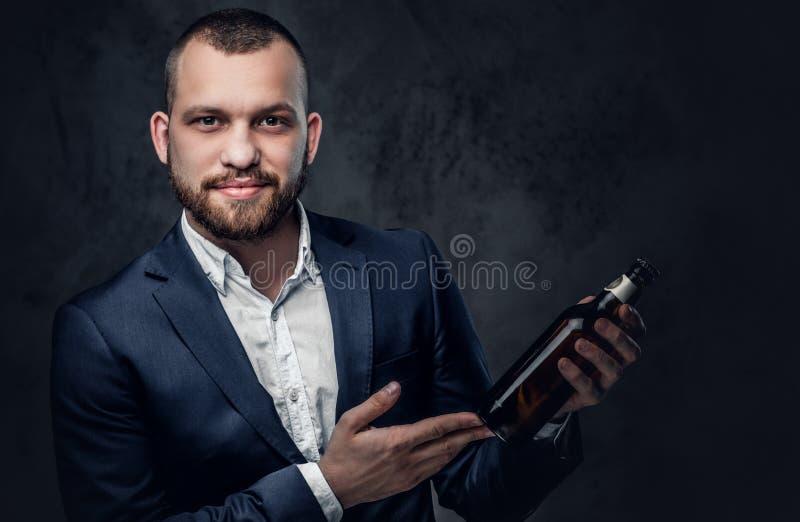 Um homem vestiu-se em um terno elegante guarda a cerveja do ofício imagem de stock