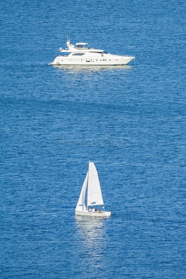 Um iate pequeno do navio e do motor de navigação na orientação vertical da imagem da água azul fotografia de stock
