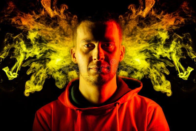 Um indiv?duo adulto est? o olhar para a frente no hoodie destacado em amarelo e em vermelho nos lados com um sorriso em um fundo  imagens de stock royalty free