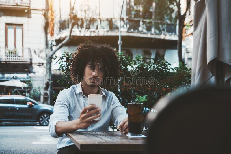 Um indivíduo asiático com ar livre do telefone celular e do cocktail imagens de stock