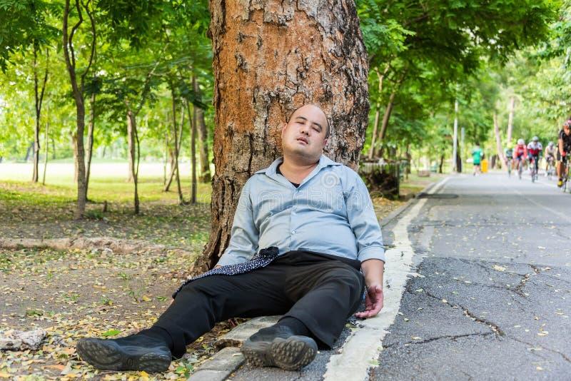 Um indivíduo asiático gordo que dorme sob a árvore ao lado da rua foto de stock