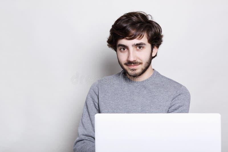 Um indivíduo atrativo seguro com barba escura e o penteado à moda que sentam-se na frente do laptop aberto que tem o lo encantado fotografia de stock