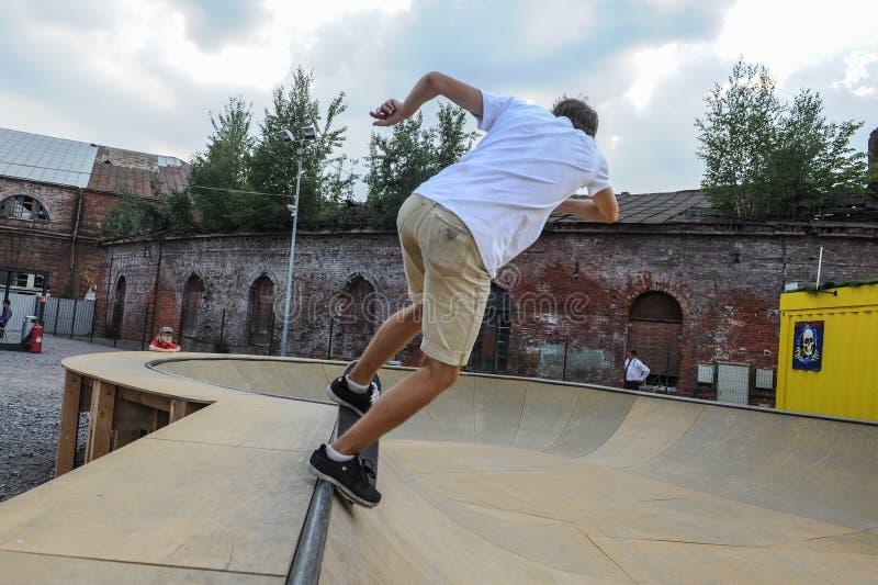 Um indivíduo com o seu para trás está estando em um skate em cima Área do entretenimento da cidade ensolarado imagem de stock royalty free
