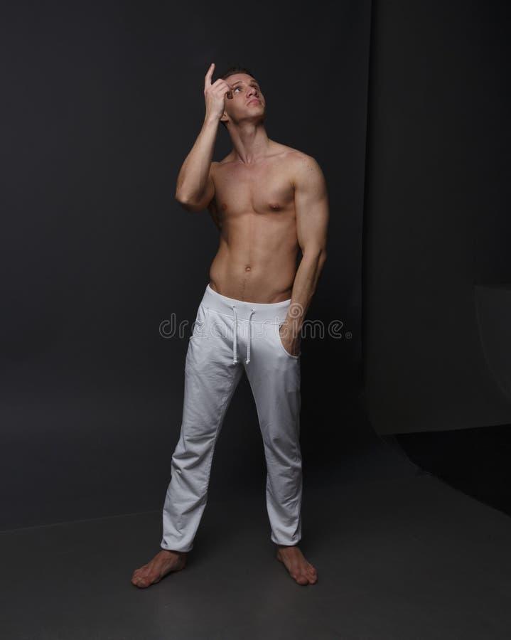 um indivíduo com um torso despido, nas calças brancas, e em uma camisa branca, está em um fundo cinzento imagens de stock