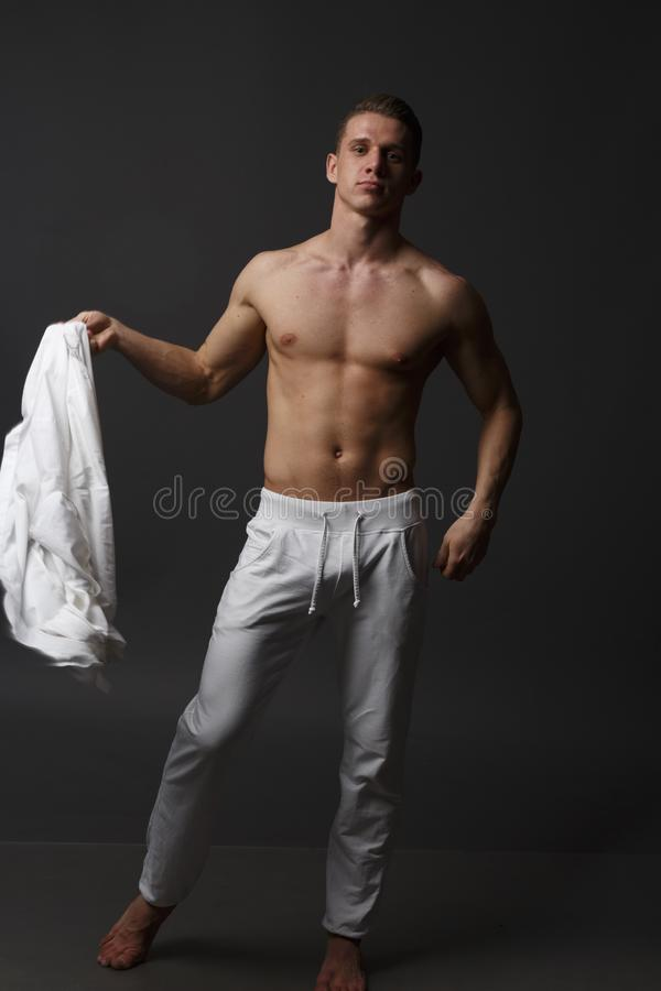um indivíduo com um torso despido, nas calças brancas, e em uma camisa branca, está em um fundo cinzento imagem de stock