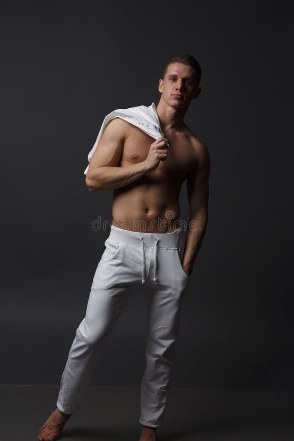 um indivíduo com um torso despido, nas calças brancas, e em uma camisa branca, está em um fundo cinzento fotografia de stock