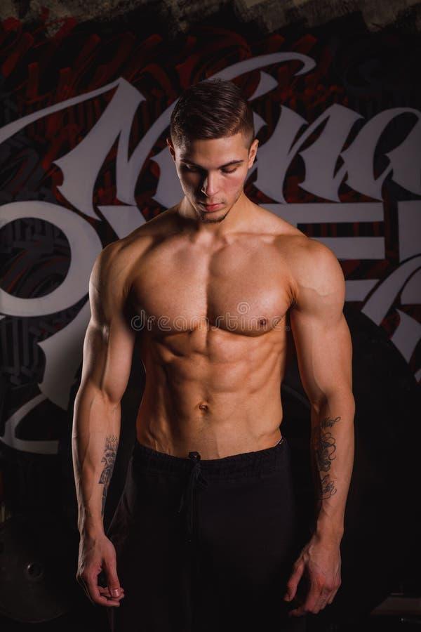 Um indivíduo considerável, está e olha para baixo com um olhar sério Dentro no gym foto de stock