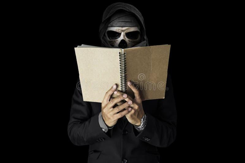 Um indivíduo do crânio no caderno preto da leitura do terno, no fundo escuro preto do ambiente foto de stock