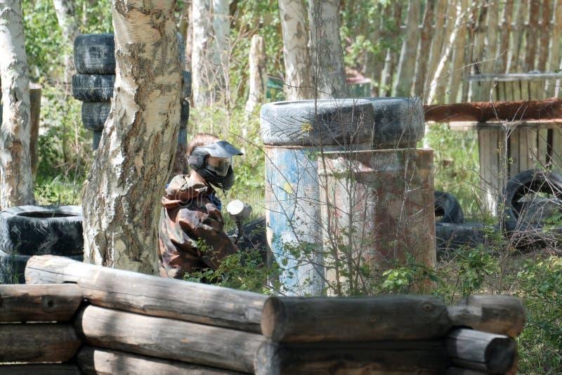 Um indivíduo durante um jogo do paintball na operação de descarga Terno da camuflagem, máscara protetora e armas Pneus, tambores, foto de stock royalty free