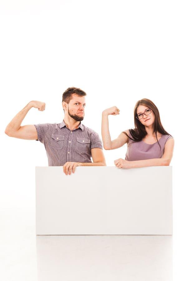 Um indivíduo e uma menina estão levantando com um sinal branco, cartão, um sinal em suas mãos fotografia de stock