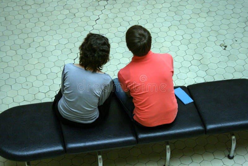 Um indivíduo e uma menina que sentam-se em um banco ombro a ombro, no borrão e no efeito da grão imagens de stock