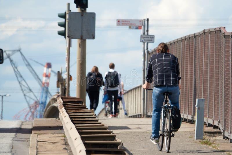 Um indivíduo em uma camisa e na calças de ganga está montando uma bicicleta da estrada para trabalhar em um dia ensolarado do ver imagem de stock royalty free