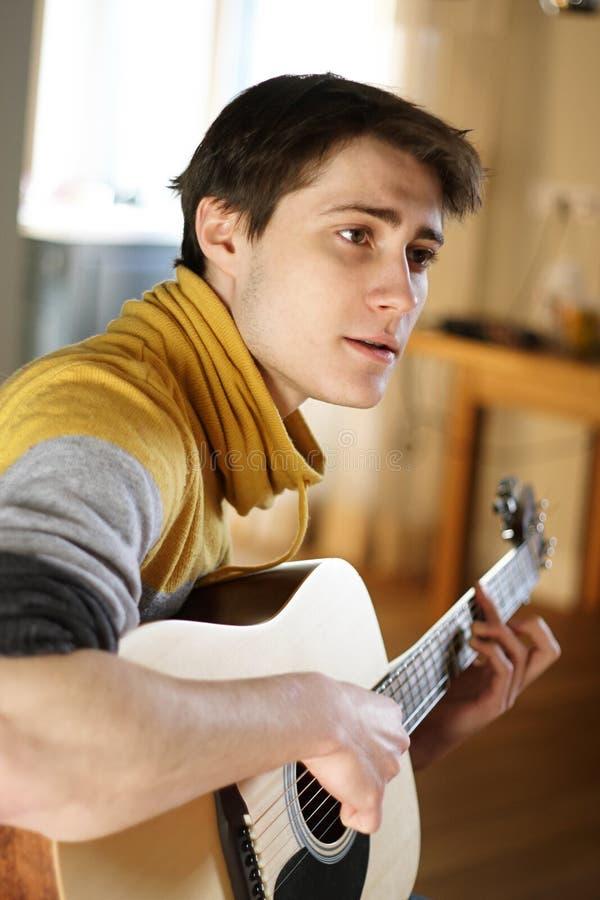 Um indivíduo em uma camiseta amarela canta uma música, jogando em sua guitarra imagem de stock royalty free