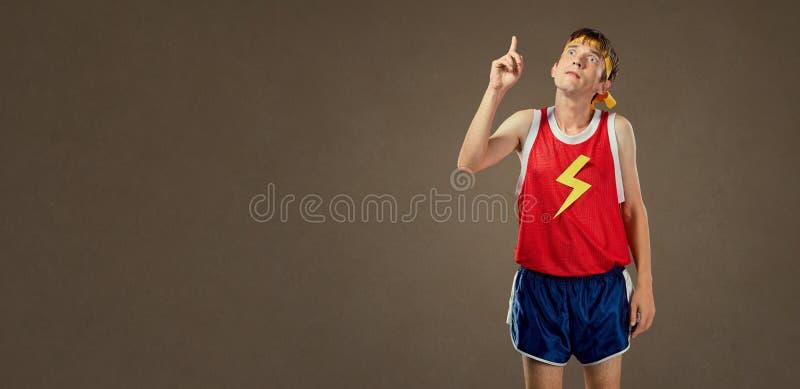 Um indivíduo engraçado fino na roupa dos esportes mostra seu dedo acima fotografia de stock