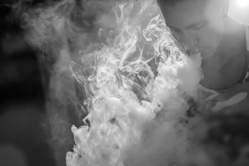 Um indivíduo está fumando o cigarro eletrônico foto de stock royalty free
