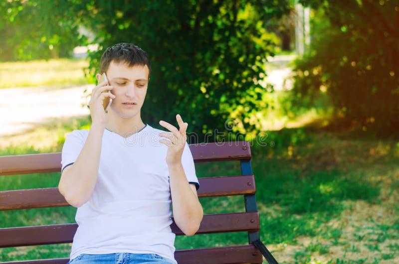 Um indivíduo europeu novo em um t-shirt branco fala no telefone e senta-se em um banco no parque da cidade O homem olha seus dedo fotografia de stock