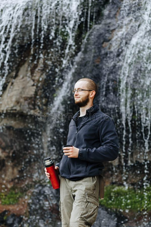Um indivíduo novo bebe o chá ou o café de uma garrafa térmica, estando perto de uma cachoeira nas montanhas foto de stock