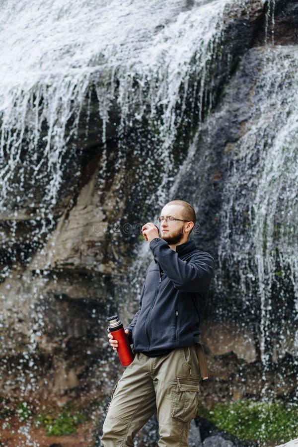 Um indivíduo novo bebe o chá ou o café de uma garrafa térmica, estando perto de uma cachoeira nas montanhas imagens de stock royalty free