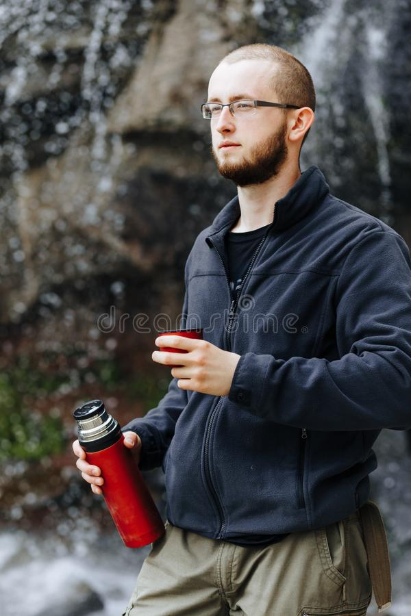 Um indivíduo novo bebe o chá ou o café de uma garrafa térmica, estando perto de uma cachoeira nas montanhas imagem de stock